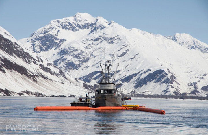 boat and containment boom on water with mountain in background