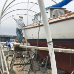Man building work scaffolding around a boat
