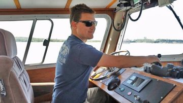 Young man at the controls of a boat
