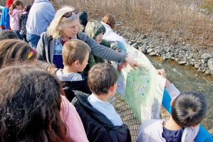 Woman with a class of young children standing by a stream, looking at a map