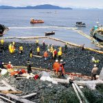 workers on a beach during and oil spill