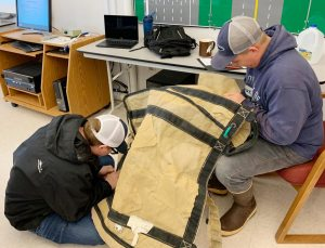 Two students practice repairing a large brailer bag