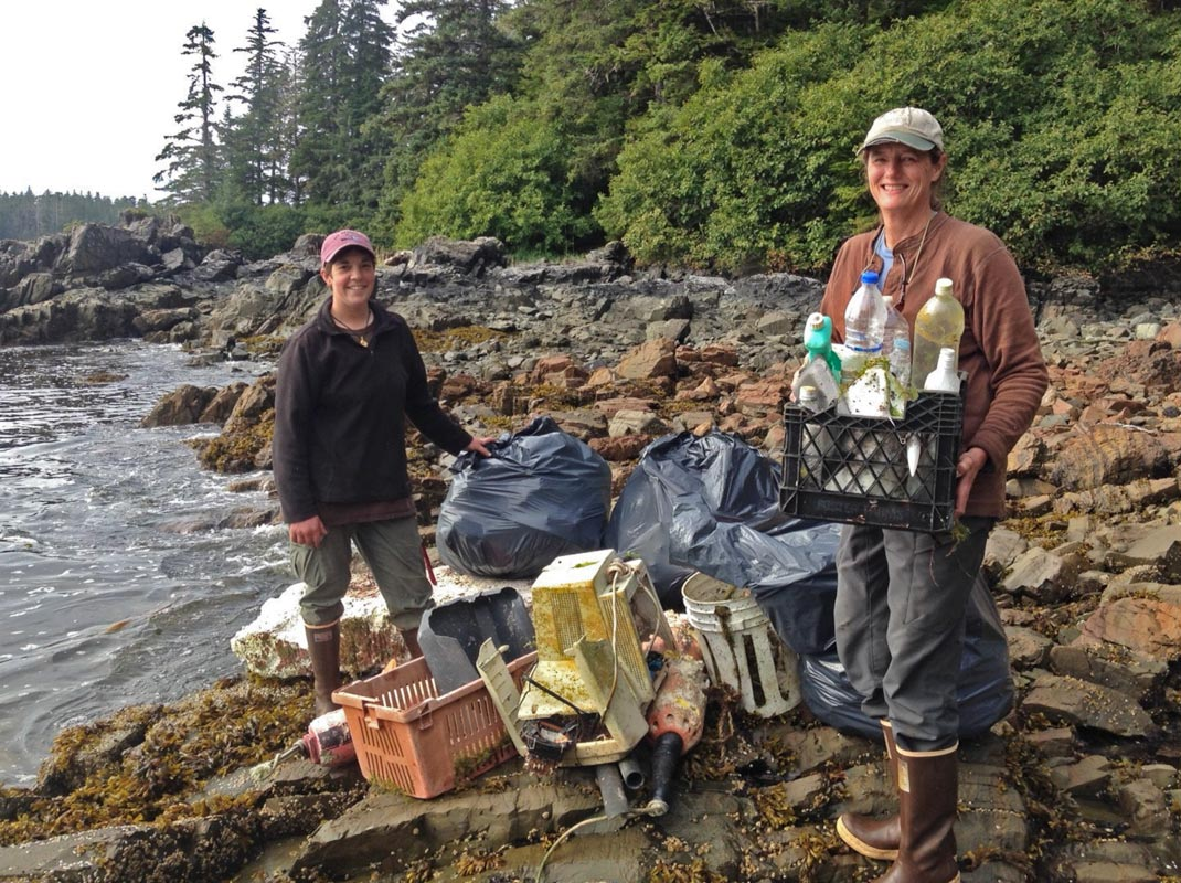 Two women on coast with collection of plastic marine debris