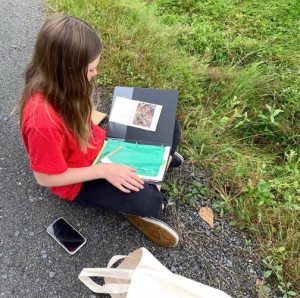 Girl outdoors with science notebook