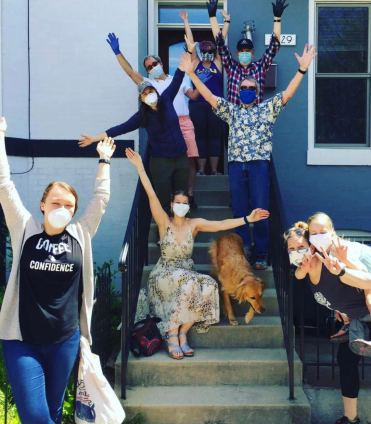 Ann-Christine Zinkann with NOAA colleagues on the steps outside her home, wearing masks and raising arms in celebration of her graduation.