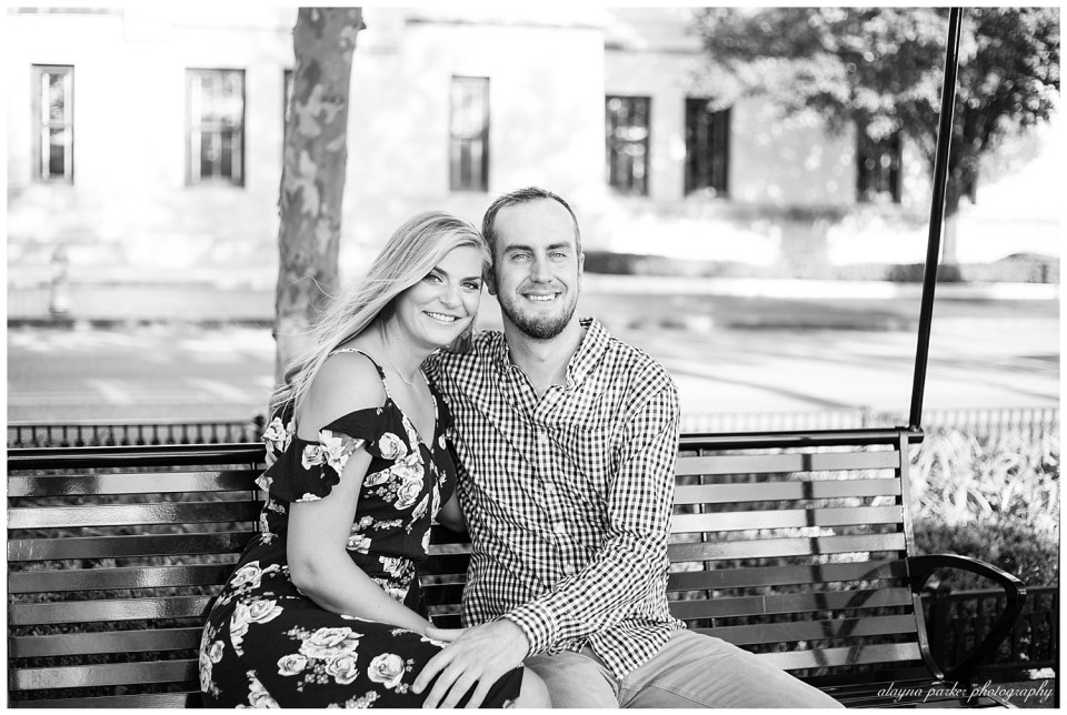 A photograph in black and white of an engaged couple sitting on a bench outdoors, smiling as they lean in against each other  by Alayna Parker  - Columbus Ohio engagement photography