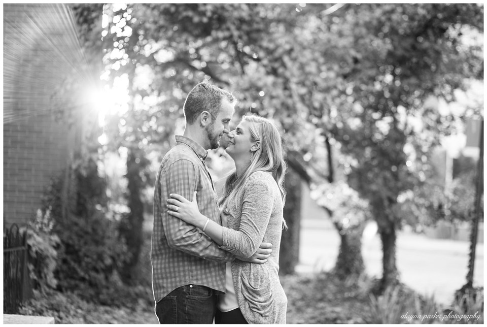 A photograph in black and white of a couple newly engaged, standing outside, romantically gazing at each other