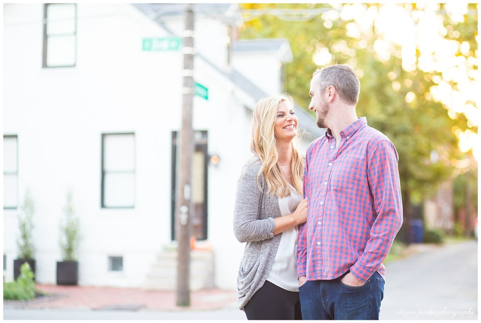 An image of an engaged couple standing at a picturesque street corner, smiling happily at each other  by Alayna Parker  - Columbus Ohio engagement photography