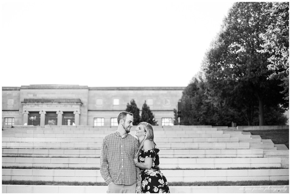 An image in black and white of a couple couple who are newly engaged, standing close as they gaze romantically at each other