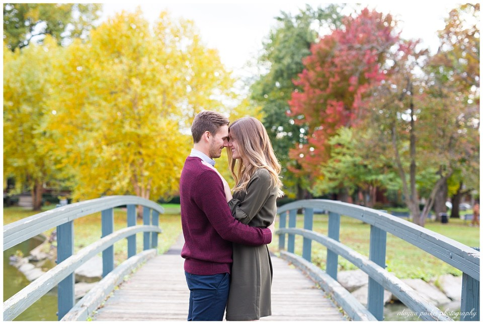 A picture of an engaged couple embracing each other as they touch foreheads, standing on a picturesque bridge with a backdrop of fall trees in German Village, near downtown Columbus by Alayna Parker  - Columbus Ohio engagement photographers