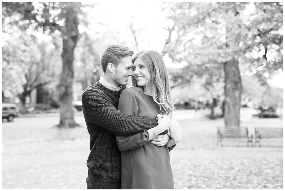 An image in black and white of a fiance holding his partner from behind, as they smile at each other in an outdoor setting in the German Village neighborhood in Columbus OH by Alayna Parker Photography  - Columbus OH engagement photographer