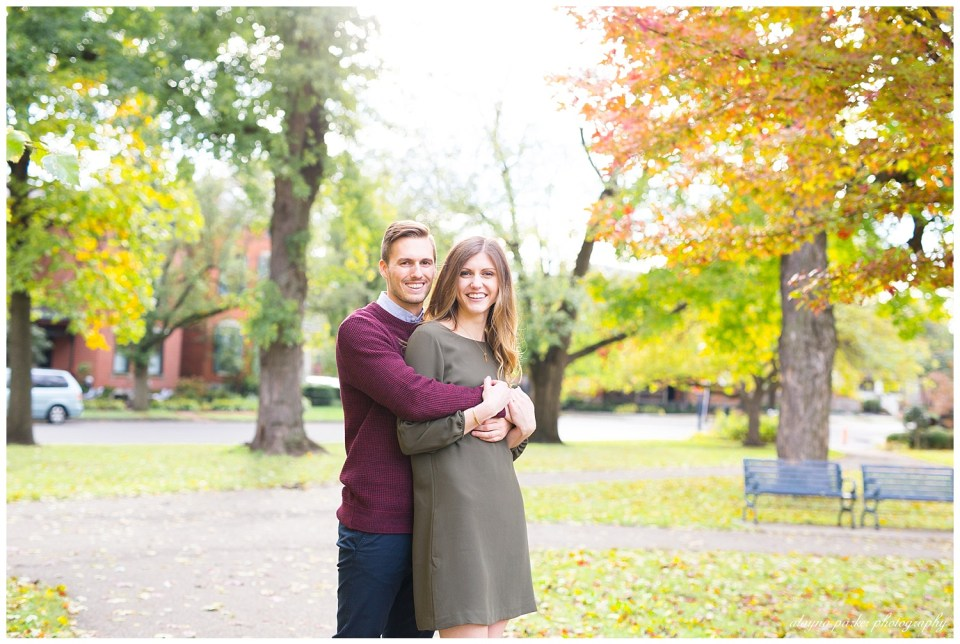 An image of an engaged man holding his partner from behind as they stand close and smile with a backdrop of fall trees in German Village by Alayna Parker Photography  - Columbus OH engagement photographer
