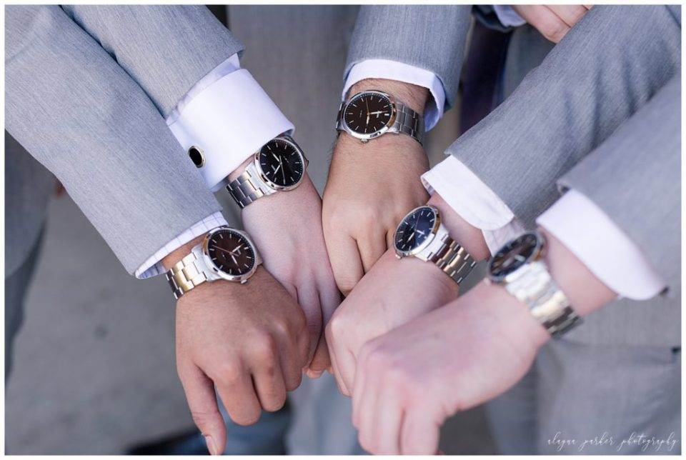 A photograph of a closeup view of the groom and his groomsmen showing their matching watches as they put their hands together at Station 67 on W Broad St in Columbus by Alayna Parker Photography  - Columbus OH wedding photography