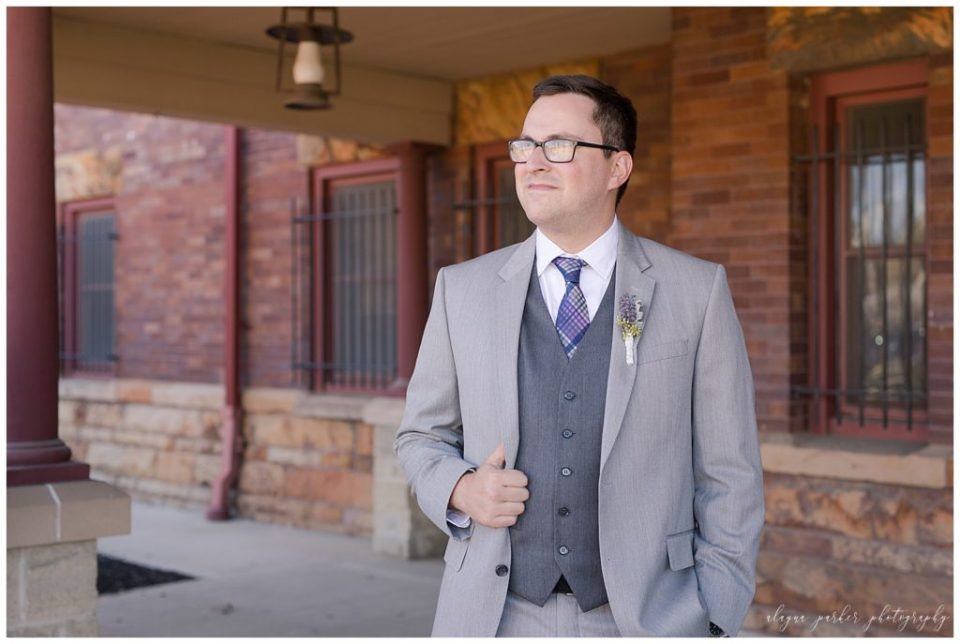 A photograph of the groom in his handsome gray tuxedo, pausing shortly before the wedding at Sation 67 in downtown Columbus by Alayna Parker  - Columbus OH wedding photography
