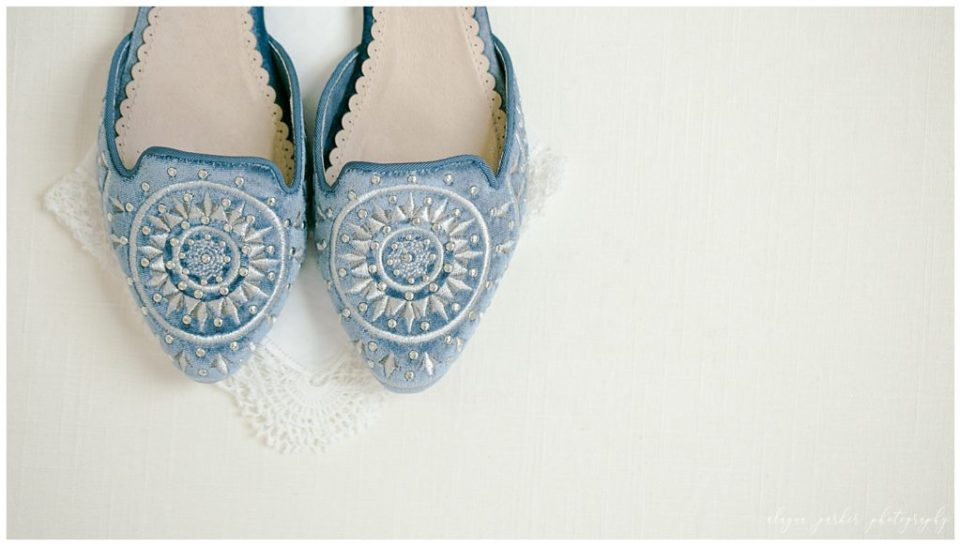 A picture of a closeup view of the bride's beautiful embroidered blue shoes before she slips them on for the wedding at Station 67 , near the Scioto River by Alayna Parker Photography  - Columbus  wedding photographers