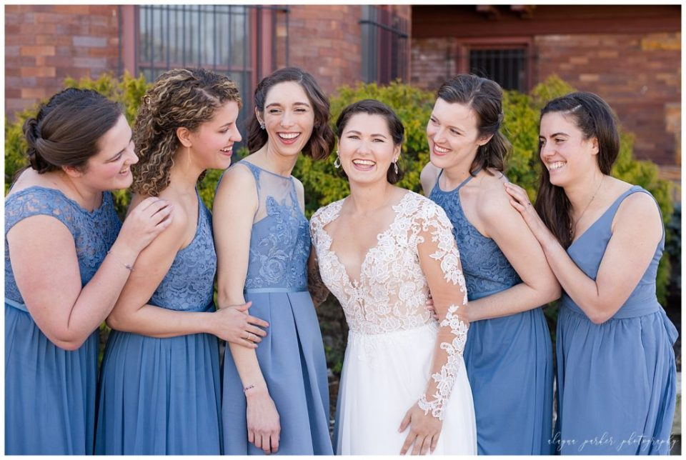 An image of the bride laughing casually with her bridesmaids in their beautiful wedding attire at Station 67 on W Broad St in Columbus by Alayna Parker Photography  - Columbus Ohio