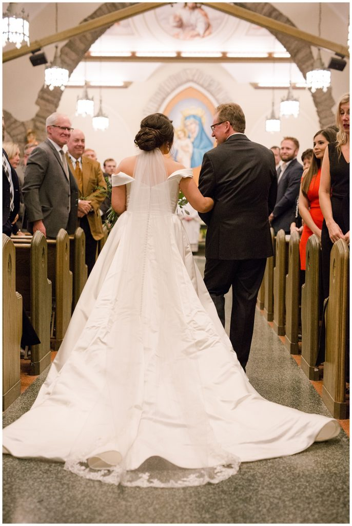 A photograph of the bride and her father from behind as they walk down the aisle at the church wedding and the guests look on by Alayna Parker  - Columbus OH marriage photographer