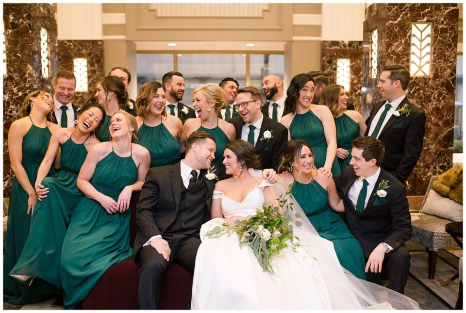 A picture of a casual moment with the bride and groom and their wedding party, smiling and laughing together at the Hotel LeVeque in Downtown Columbus by Alayna Parker  - Columbus  wedding photography