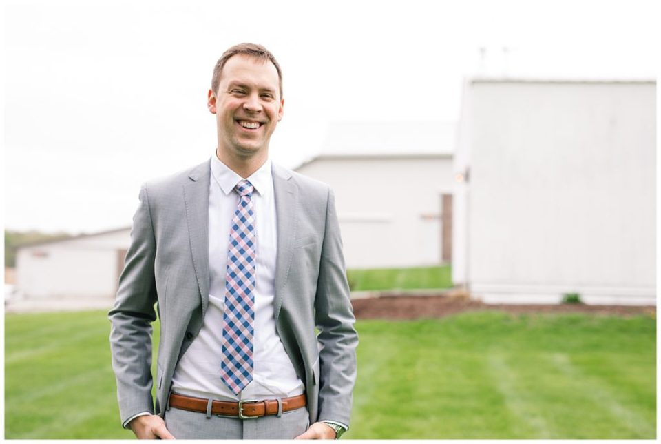 An image of the groom smiling in his gray tuxedo, relaxed and ready for the wedding to start soon at the Buckeye Barn wedding venue by Alayna Parker Photography  - Columbus Ohio wedding photographer