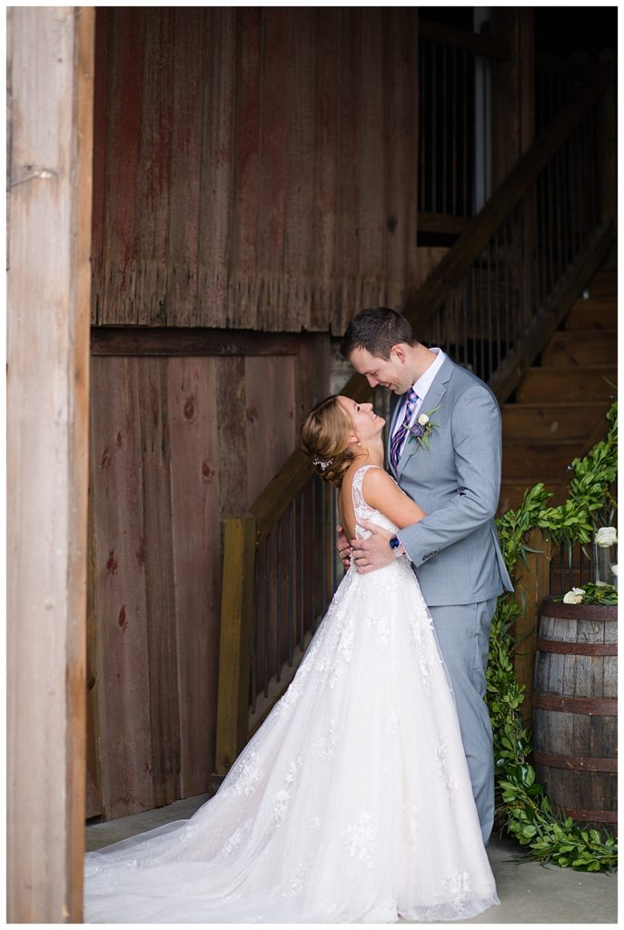 A photograph of a bride and groom holding each other close as they stand in their beautiful wedding clothes in a rustic barn setting at the Buckeye Barn wedding venue by Alayna Parker Photography  - Columbus OH wedding pictures