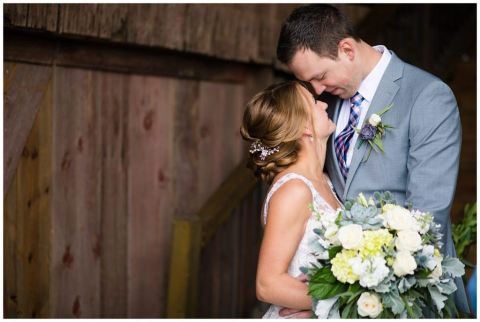 An image of a bride and groom touching foreheads as they hold each other romantically in a rustic barn setting at the Buckeye Barn by Alayna Parker Photography  - Columbus Ohio marriage photography