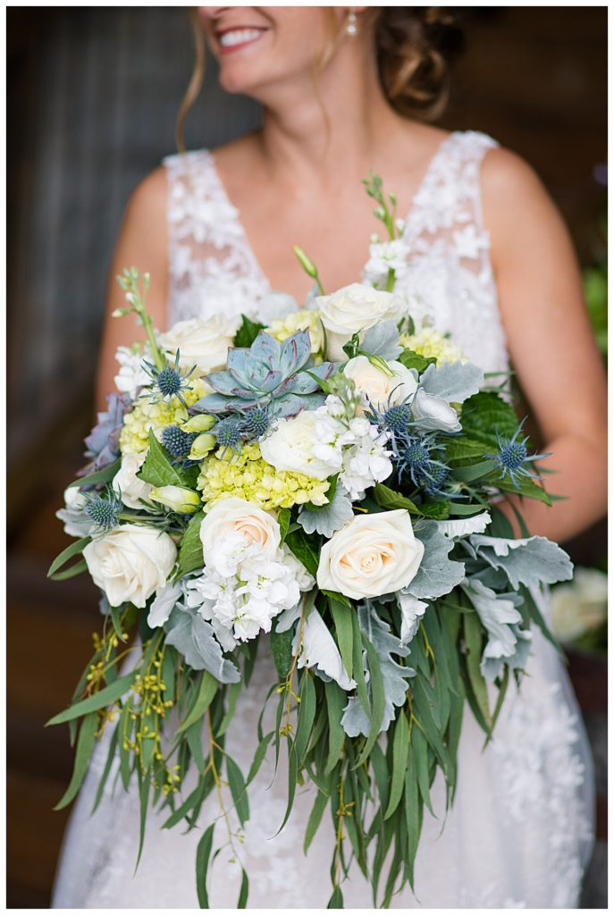 A photograph with a closeup of the bride's beautiful bouquet of roses and blue-gray flowers at the Buckeye Barn by Alayna Parker Photography  - Columbus OH wedding photographers