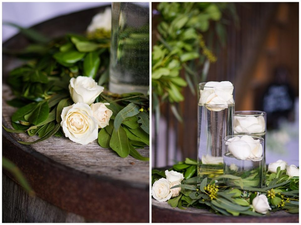 A photograph of white roses and dark green leaves decorating tables at the wedding hall, and another view of centerpieces with floating roses at the Buckeye Barn in Piqua Ohio by Alayna Parker  - Columbus OH wedding images