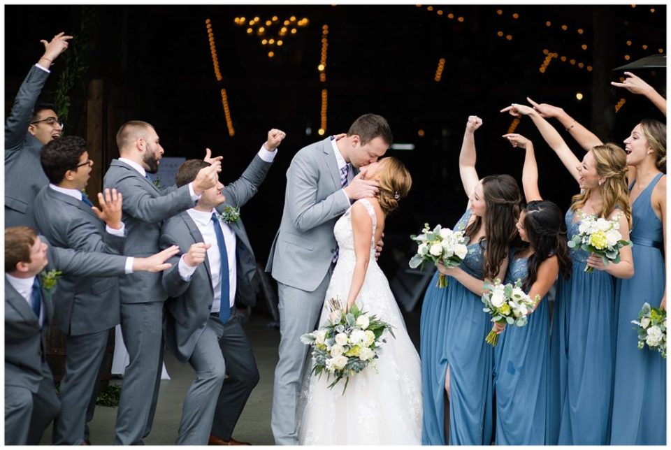 An image of a bride and groom kissing in the wedding hall while their wedding party cheers them on at a Buckeye Barn wedding by Alayna Parker  - Columbus Ohio marriage photographer