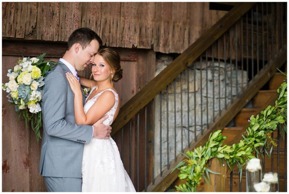 A picture of the bride and groom holding each other tenderly as they stand together in a beautiful barn setting at the Buckeye Barn in Piqua Ohio by Alayna Parker  - Columbus  wedding photography