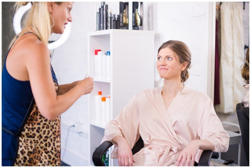 bride smiling at makeup artist while getting makeup done