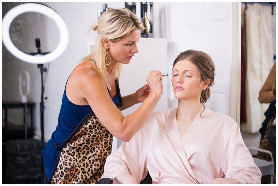 makeup artist applying mascara to bride