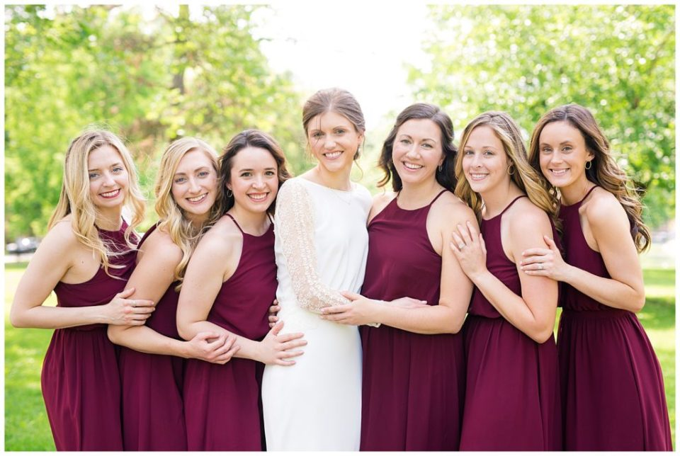 bride and bridesmaids hugging each other smiling at camera