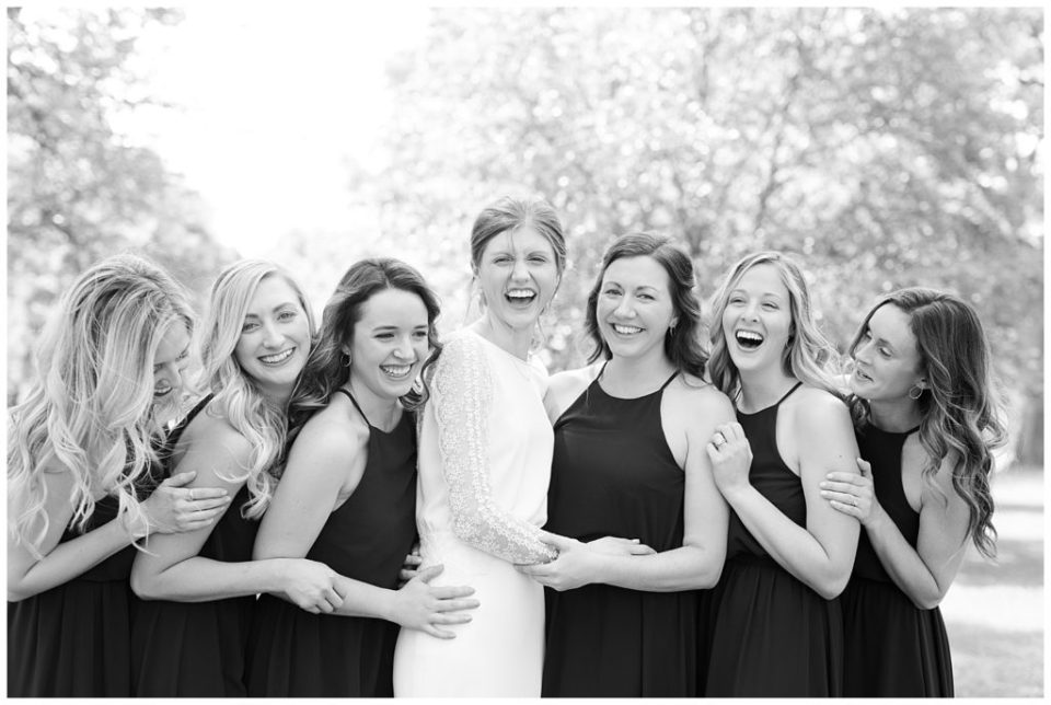 A photograph in black and white of a bride laughing and relaxing with her bridesmaids in an outdoor setting at Dock 580 wedding venue  by Alayna Parker  - Columbus OH wedding photography