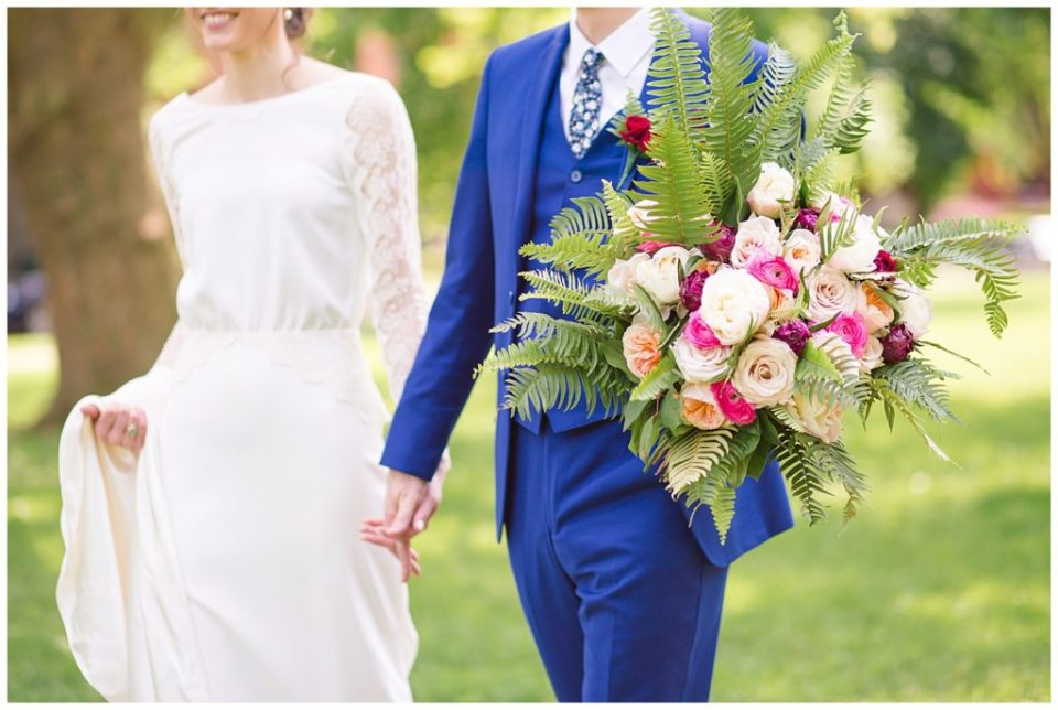 An image of the bride and groom holding hands as they walk together outdoors at Dock 580 by Alayna Parker Photography  - Columbus Ohio wedding pictures