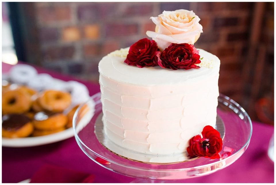 A picture of a closeup view of a wedding cake decorated with real roses, resting on a table at the wedding reception at Dock 580, in the hostoric Smith Bros Hardware building by Alayna Parker  - Columbus  marriage photographer