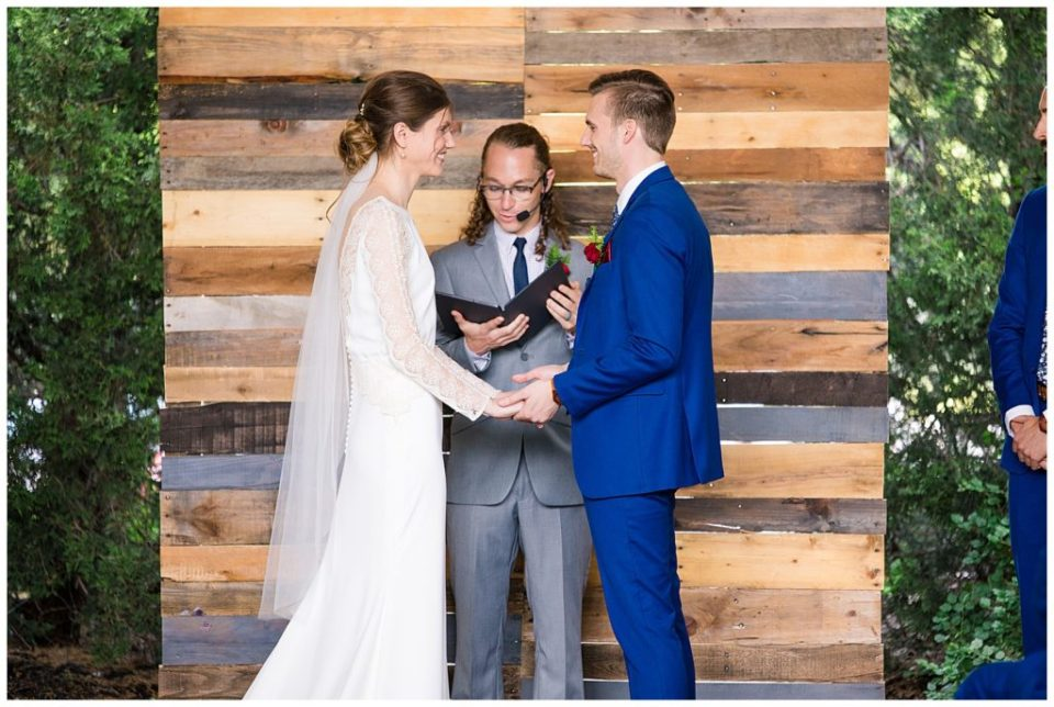 bride and groom standing in front of distressed wooden altar at dock 580