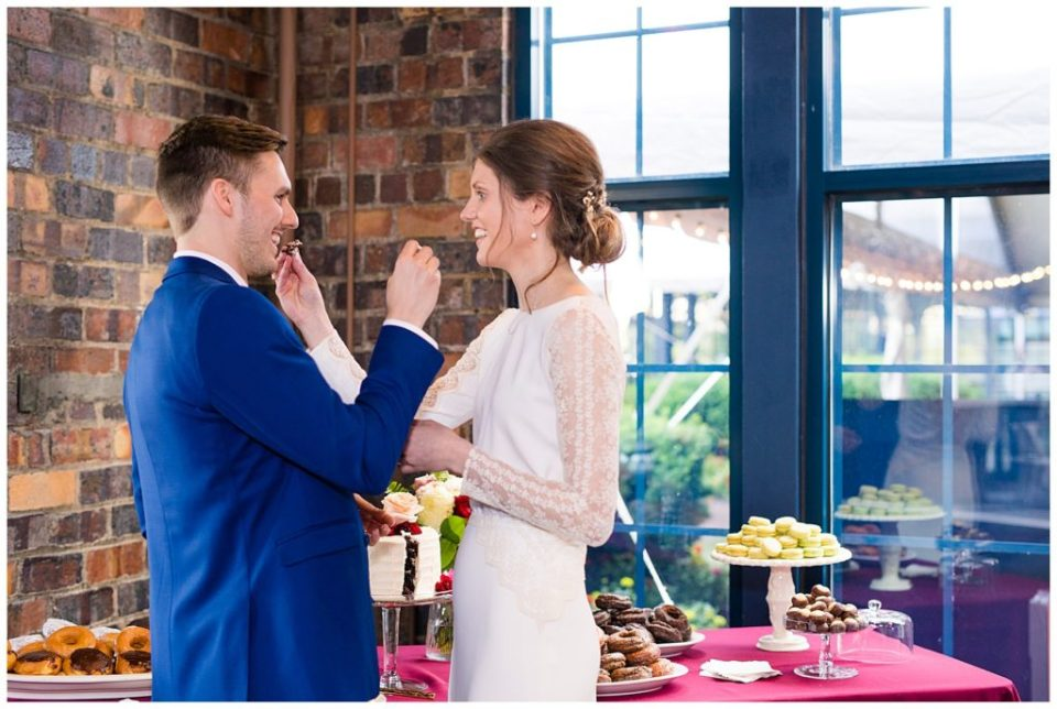 bride and groom feeding each other cake at dock 580