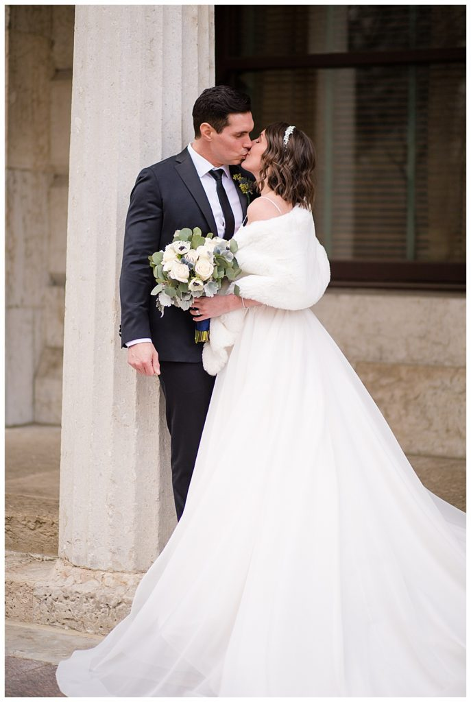 An image of a bride and groom standing close, kissing in their beautiful wedding clothes at the Ohio Statehouse by Alayna Parker  - Columbus Ohio marriage photographer