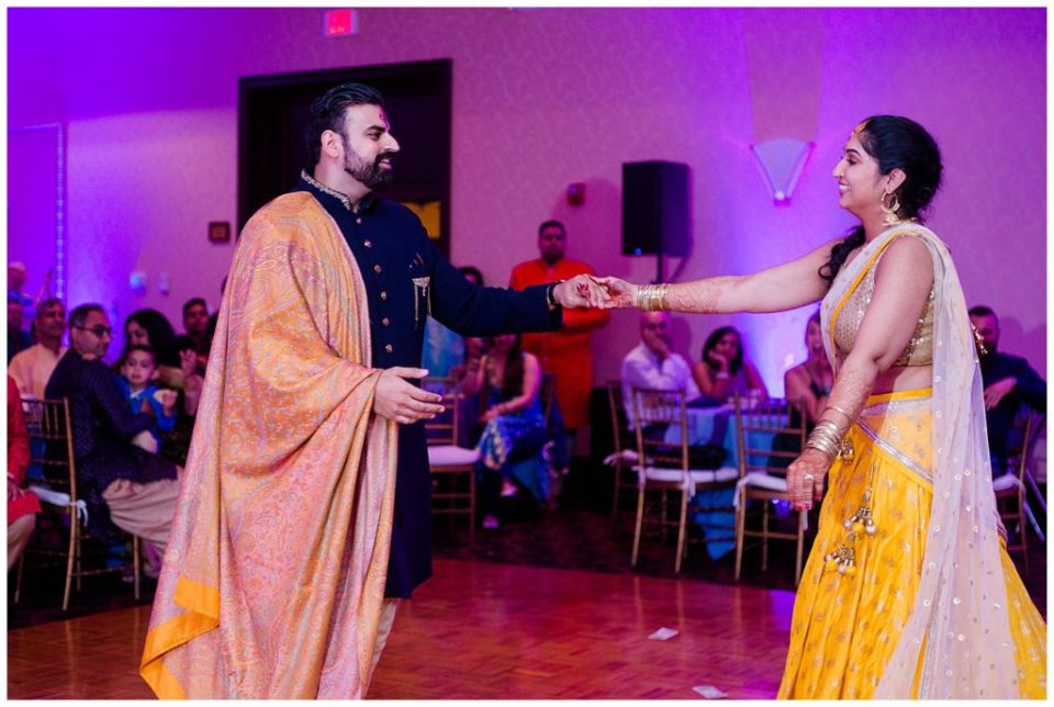 A picture of an engaged couple smiling and romantically dancing at their Hindu engagement party at the Bertram Inn and Conference Center in Aurora by Alayna Parker Photography  - Cleveland  engagement photographers