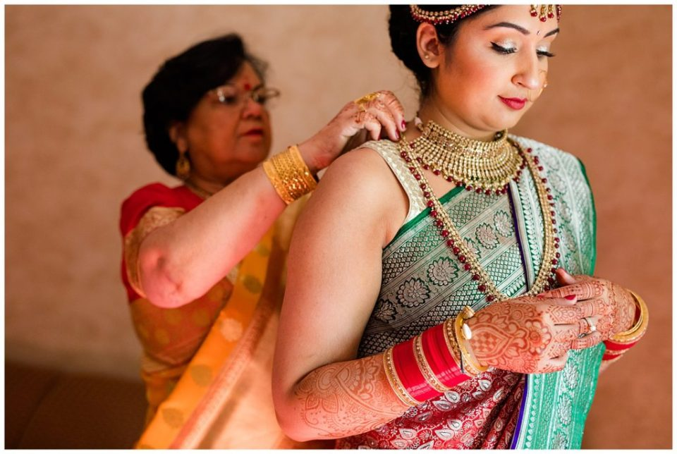mother of the bride putting on traditional indian jewelry
