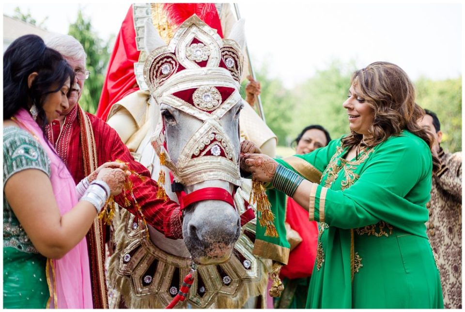 groom's sisters decorating horse for baraat