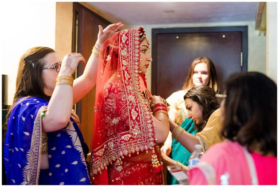 An image of an Indian bride getting dressed in a beautiful traditional sari for her wedding at the Bertram Inn wedding venue by Alayna Parker Photography  - Akron Ohio wedding photographer