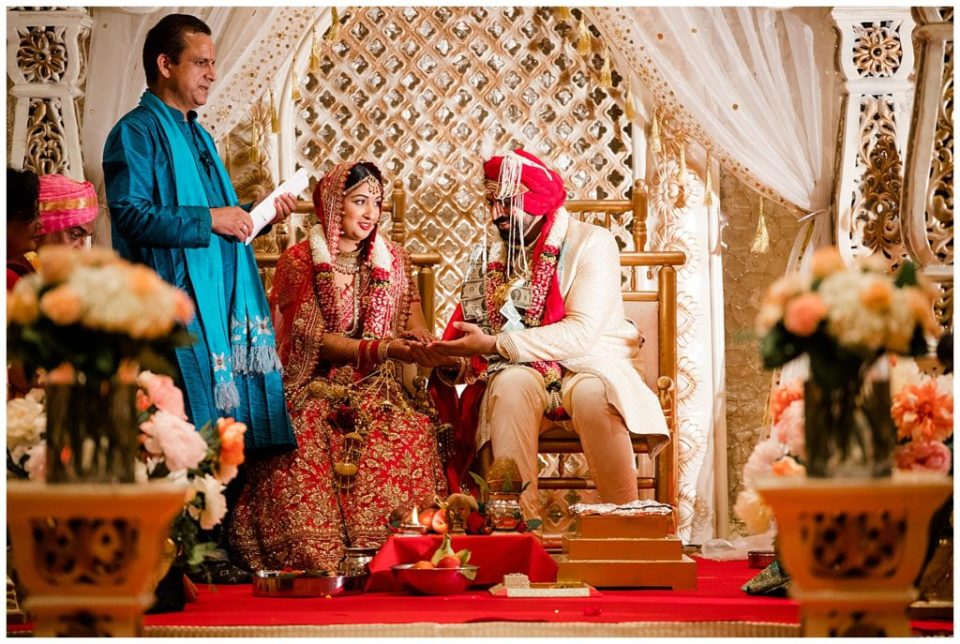 A photograph of a closeup view of the bride and groom seated on a stage in the temple with the priest as the Hindu wedding begins at the Bertram Inn wedding venue by Alayna Parker Photography  - Akron OH hindu marriage photography