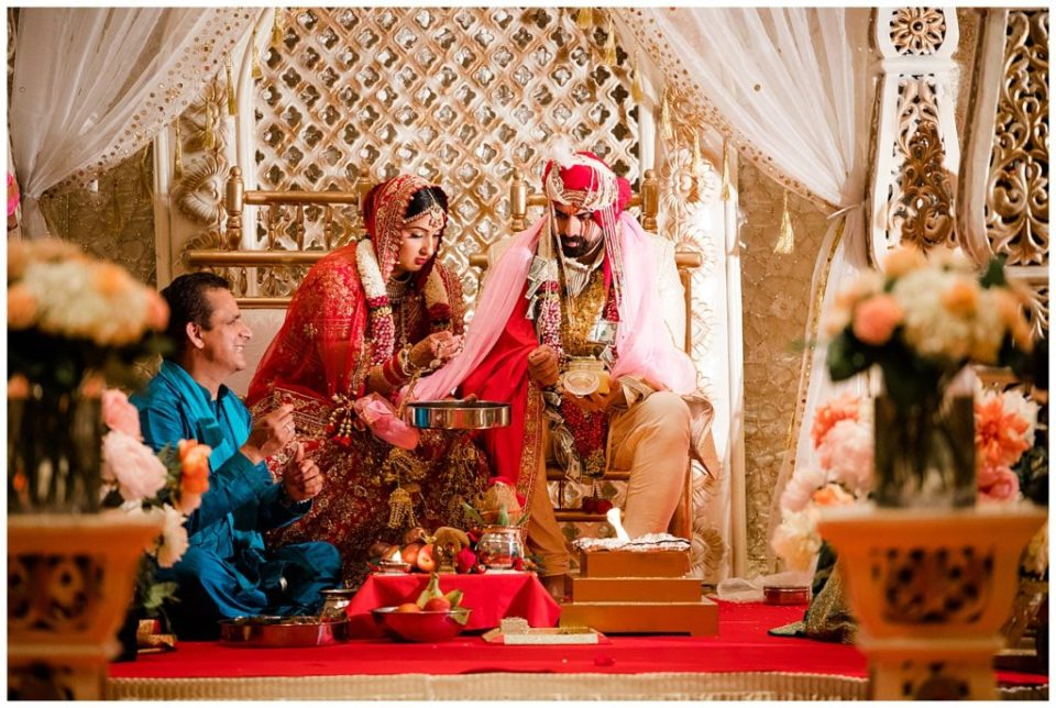 A photograph of an Indian bride and groom seated in their colorful clothes while in prayer during their Hindu wedding ceremony at the Bertram Inn and Conference Center in Aurora by Alayna Parker  - Cleveland OH wedding photographer
