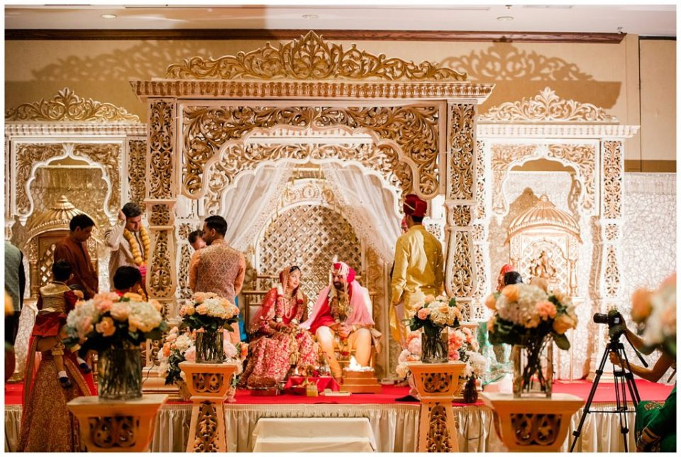 A picture of a long-range view of the bride and groom seated under an elaborate arch on stage as they smile at each other during the Hindu wedding ceremony at the Bertram Inn wedding venue by Alayna Parker Photography  - Akron  wedding photography