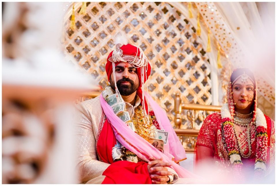 A picture of an Indian bride and groom seated in their beautiful clothes during their Hindu wedding ceremony at the Bertram Inn and Conference Center in Aurora by Alayna Parker  - Cleveland  hindu marriage photography