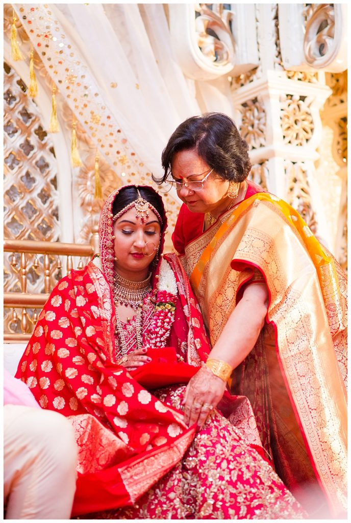 A photograph of a closeup view of an Indian bride seated during the Hindu wedding rituals while her mother adjusts her sari. at the Bertram Inn wedding venue in Aurora, Ohio by Alayna Parker  - Cleveland OH hindu wedding photography
