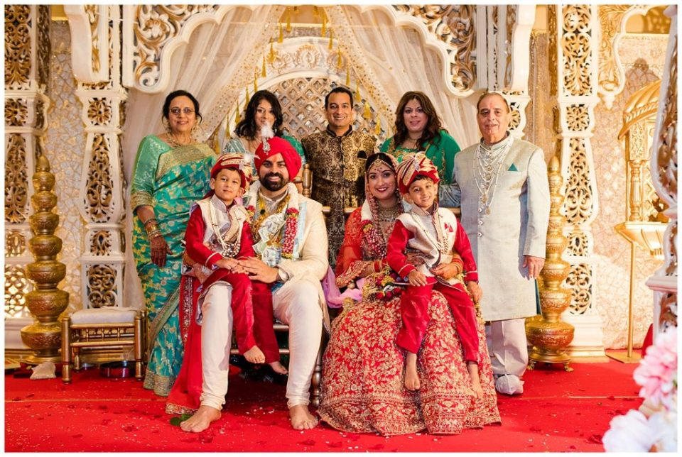 A photograph of an Indian bride and groom smiling as they pose with the groom's family after the Hindu wedding ceremony at the Bertram Inn wedding venue by Alayna Parker Photography  - Akron OH wedding photographers