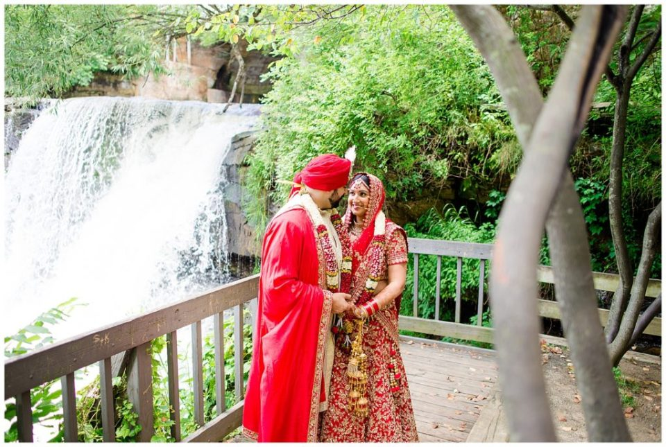 An image of an Indian bride and groom holding hands, gazing at each other as they stand outdoors after their wedding in Chagrin Falls, Ohio by Alayna Parker Photography  - Akron Ohio hindu marriage photography