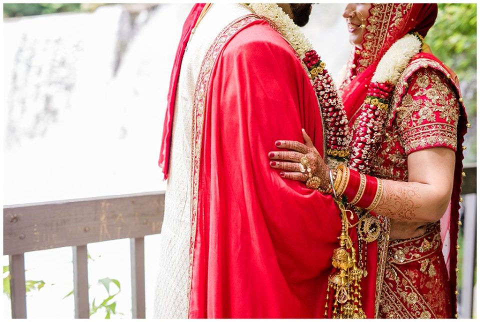 A picture of a closeup view of an Indian bride and groom holding each other close, showing the bride's elaborate jewelry and their beautiful wedding clothes in Chagrin Falls by Alayna Parker  - Cleveland  wedding photographers